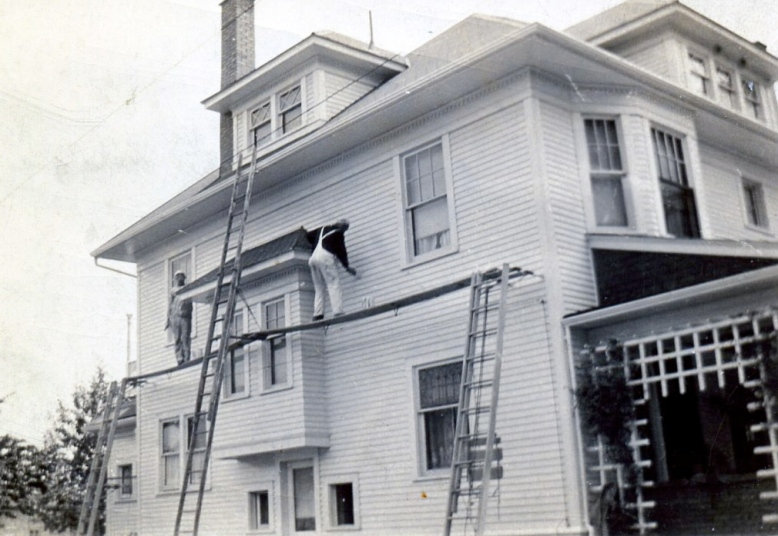 Emil and Richard Wilkens painting a house on ladders, N. Main Street, Bowling Green, Ohio. Photograph. Ca. 1950. The Wilkens Family Collection.