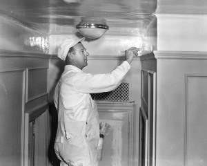 A white-clad professional painter demonstrates a new odorless Du Pont product--with a brush. Photograph. E.I. du Pont Nemours & Company. 1950s. Courtesy of the Hagley Museum and Library, digital collections, 1972341_2901.tif.