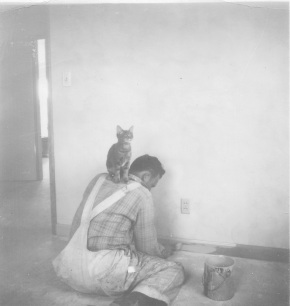 Richard Wilkens painting a room with a brush and a feline companion. Photograph. Late 1940s. The Wilkens Family Collection.