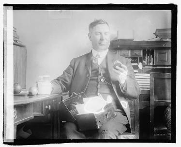 "Glass negative picturing Percy A. Quin, U.S. Representative (D-Mississippi), 26 March 1920. A caption outlines Quin's plan to counter high costs of living: ""Wear your old cloths, have them patched and darned, wear a celluloid collar, carry your lunch etc. etc."" (Courtesy of the Library of Congress, Prints & Photographs Division, LC-F8- 7276.)"