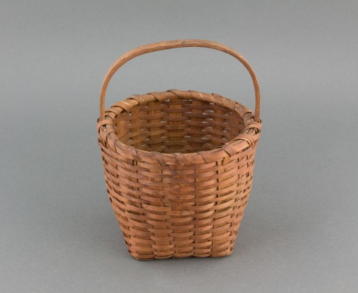 Small, ash splint gathering basket with carved handle. Square bottom, vertical sides, and round rim. Ash splint wicker weave with a checker weave base. The inner rim is carved wood with an outer, splint rim held in place with a single ash splint lash.